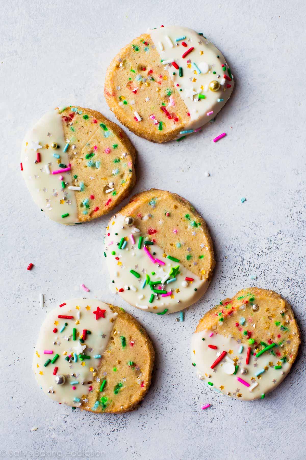 trancher les funfetti et cuire des biscuits avec la moitié de chaque biscuit trempée dans du chocolat blanc et garnie de vermicelles