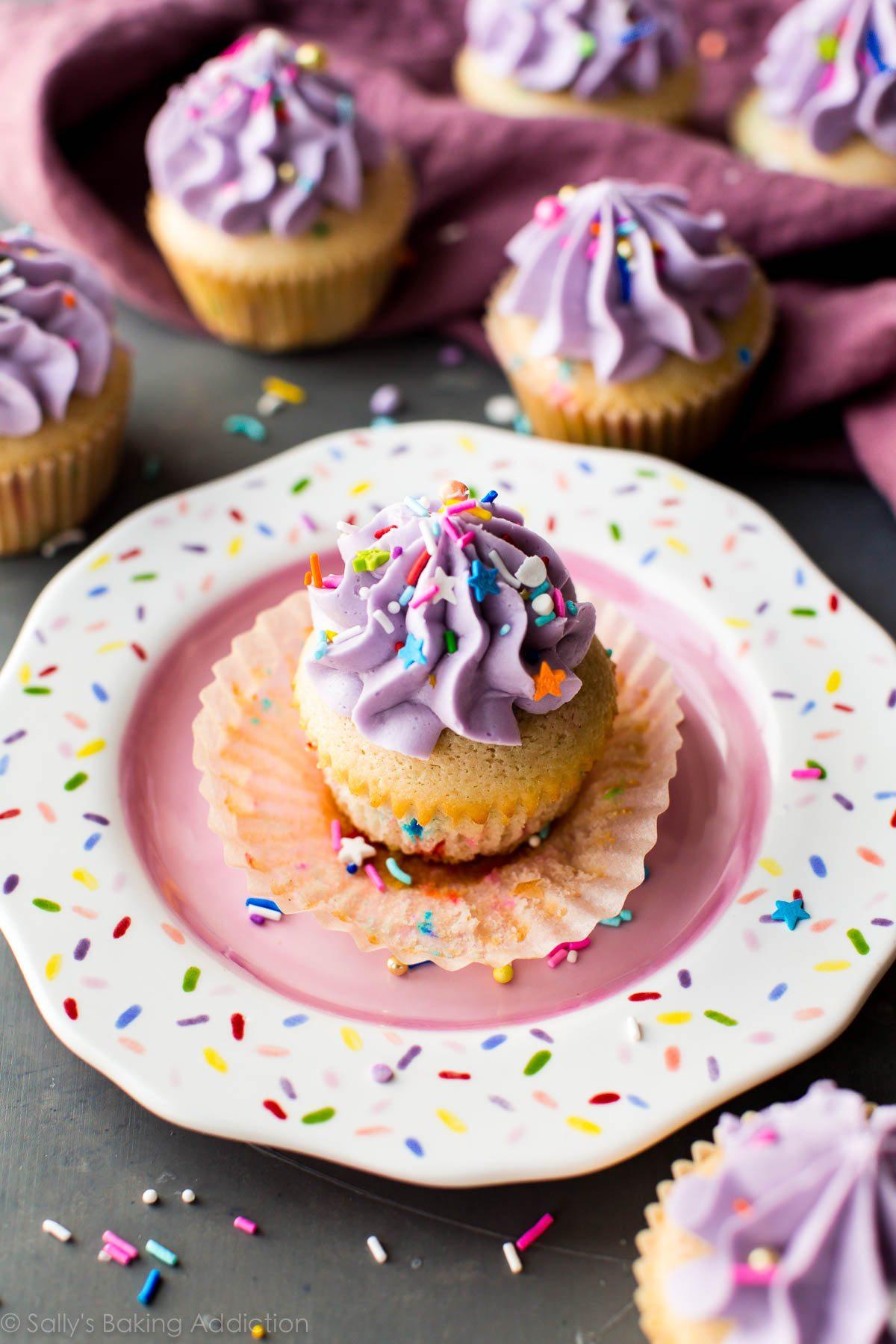 cupcake funfetti avec glaçage violet et arrose sur une assiette à saupoudrer