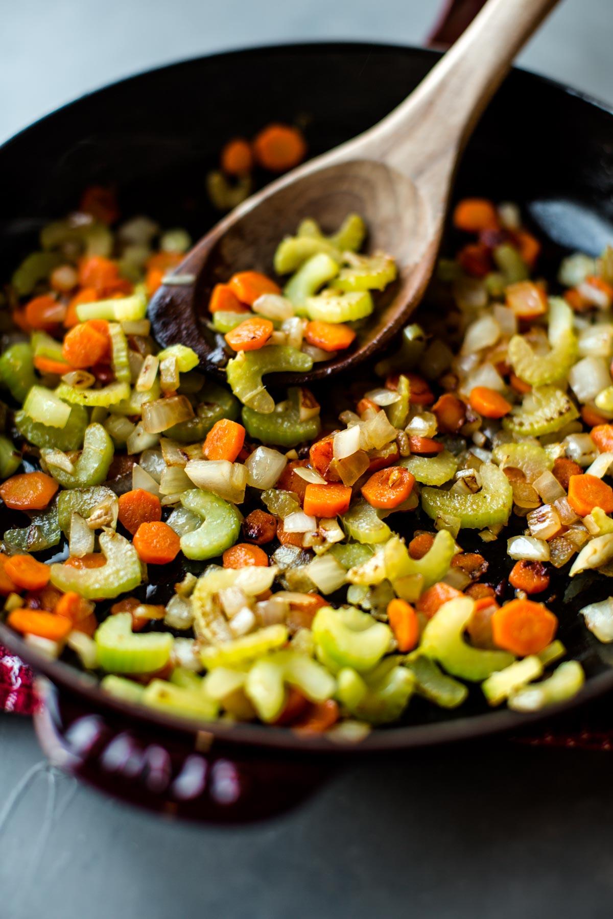 oignon, céleri et carottes sautés dans une poêle avec une cuillère en bois