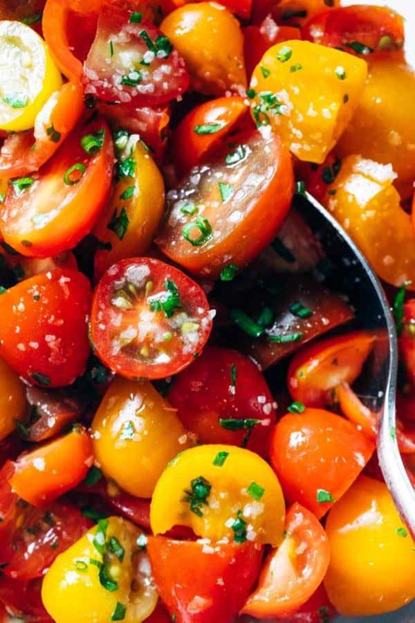 Marinated tomatoes with a spoon.