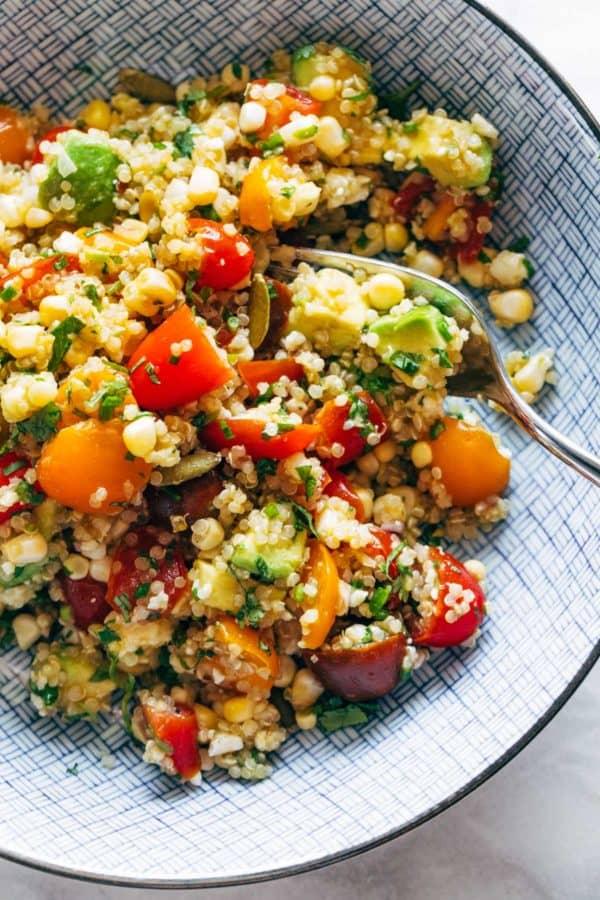 Salade de maïs, d'avocat et de quinoa dans un bol avec des tomates marinées.