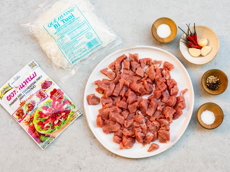Ingrédients pour nem chua présentés sur un plan de travail: porc maigre cru coupé en cubes, le sachet de salaison, peau de porc, sel, sucre, ail, grains de poivre et piments