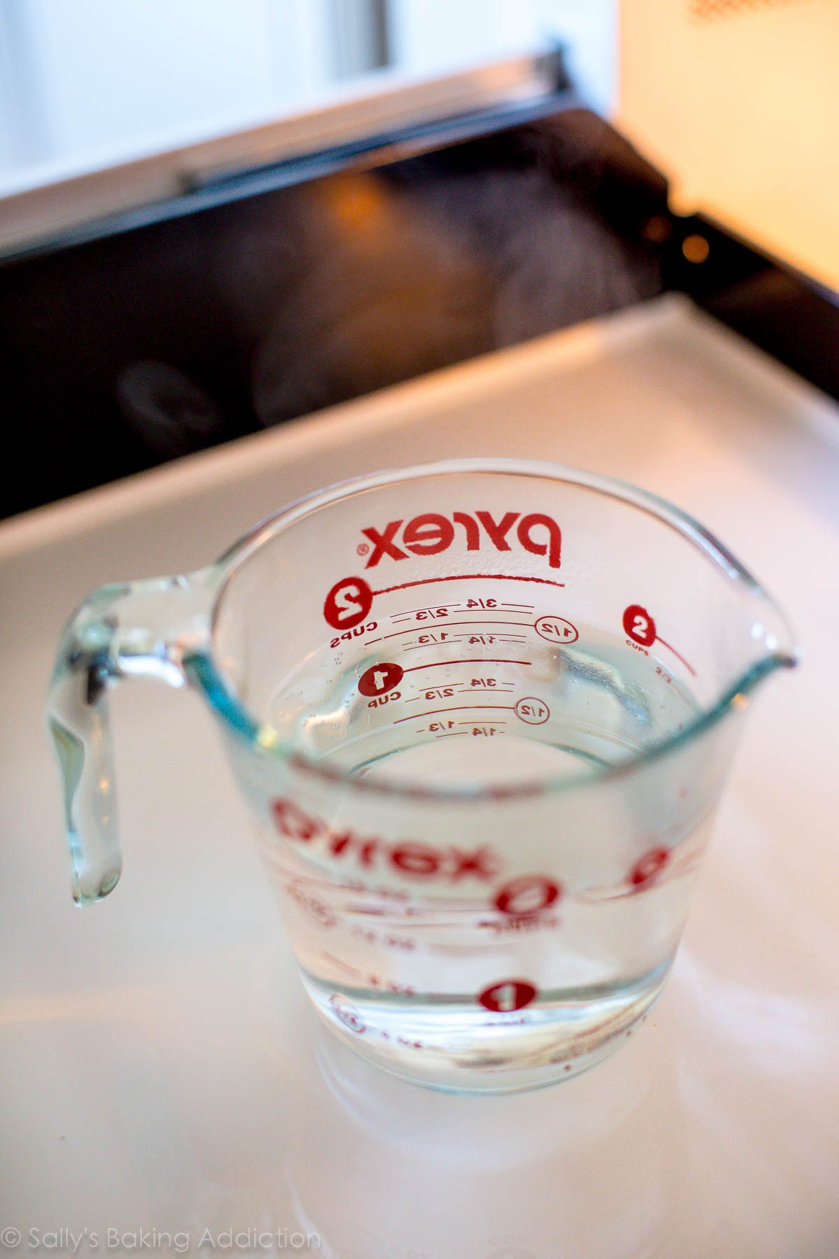 tasse à mesurer en verre remplie d'eau chaude