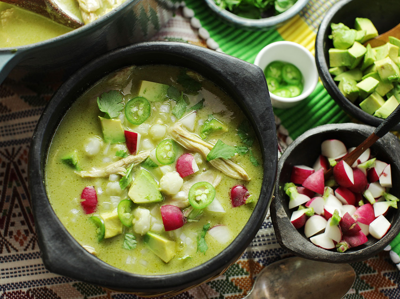 Un bol de pozole verde vert vif garni d'avocat, de jalapeños, de radis et de coriandre