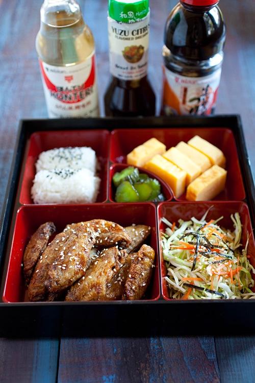 Ailes de poulet croustillantes japonaises faciles et rapides servies dans une boîte à lunch bento.