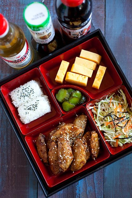 Ailes de poulet à saveur japonaise faciles garnies de graines de sésame et servies dans une boîte à bento.