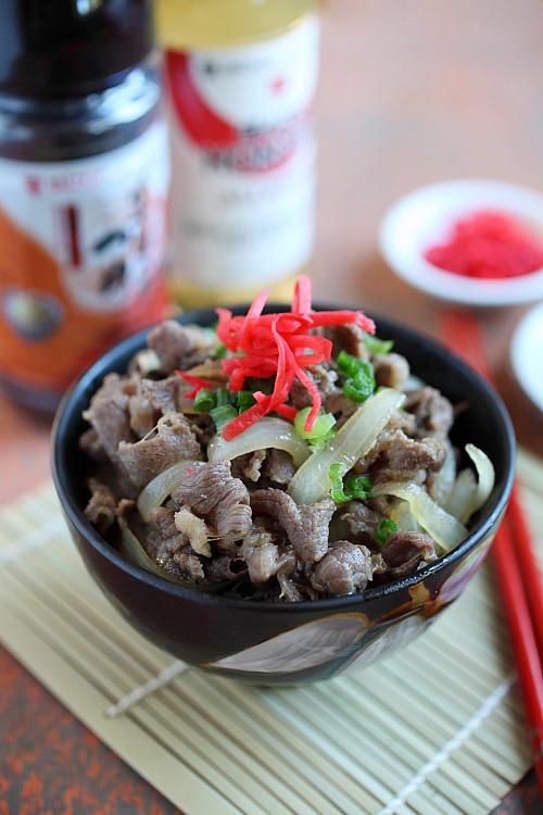 Bol de bœuf japonais Gyudon dans un plat de service garni d'oignons verts et de beni shoga.