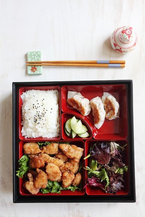Bento japonais savoureux et rapide au poulet frit avec riz cuit à la vapeur et graines de sésame, concombres marinés, salade et gyoza.