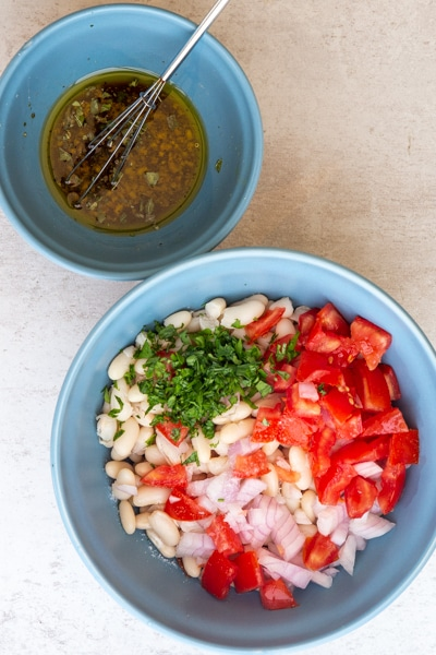 vinaigrette dans un bol bleu et les ingrédients de la salade de haricots dans un plus grand bol bleu