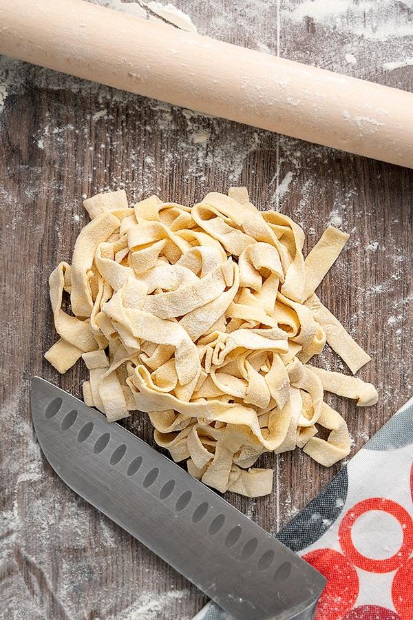 Nouilles de pâtes faites maison sur une planche brune avec un rouleau à pâtisserie et la lame d'un couteau