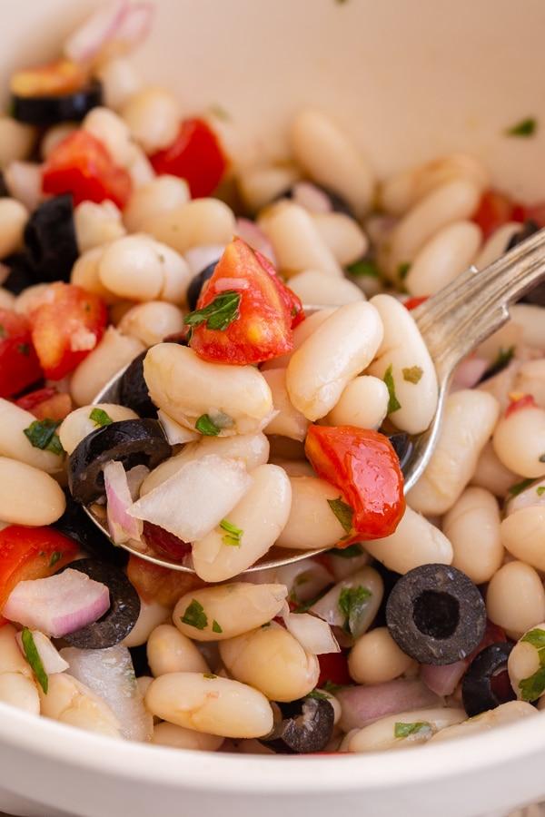 salade de haricots dans un bol blanc avec une cuillerée