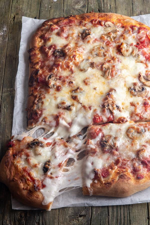 pizza sur papier sulfurisé avec une tranche coupée.