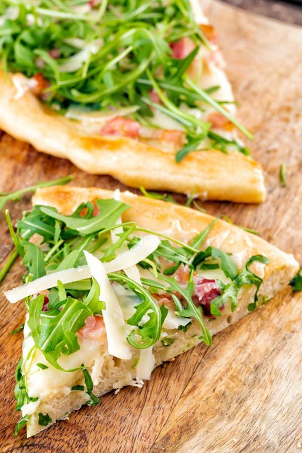 2 tranches de pizza blanche sur une planche de bois.