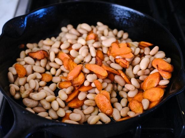 Carottes et haricots dans une poêle en fonte