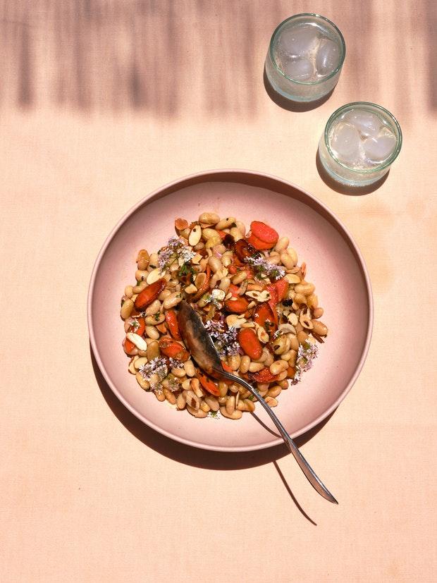 Salade de carottes, d'aneth et de haricots blancs sur une table avec deux verres